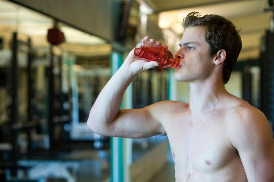 Mann trinkt einen Trainingsbooster