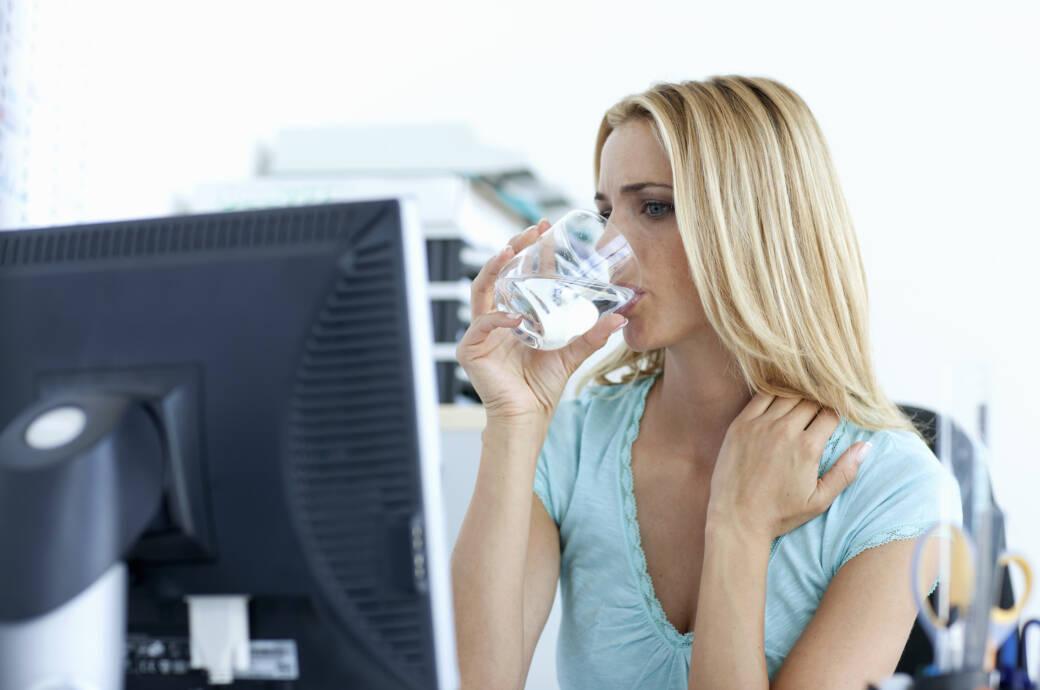 Durst gehört zu den möglichen Diabetes-Symptomen: Frau trinkt Wasser im Büro