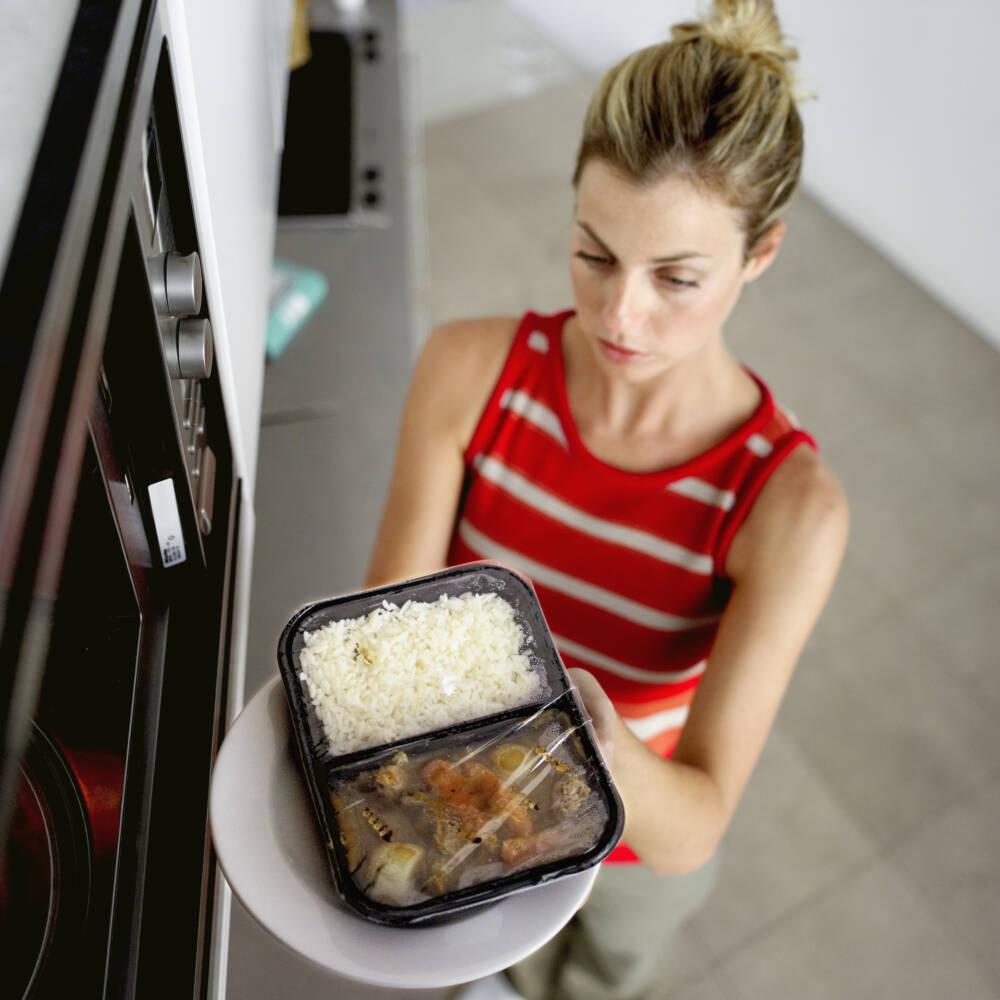 Frau schiebt Fertiggericht in die Mikrowelle