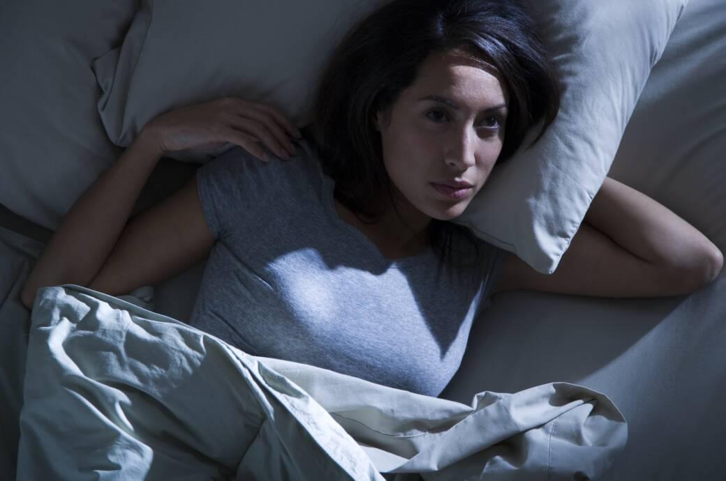 Frau liegt wach im Bett