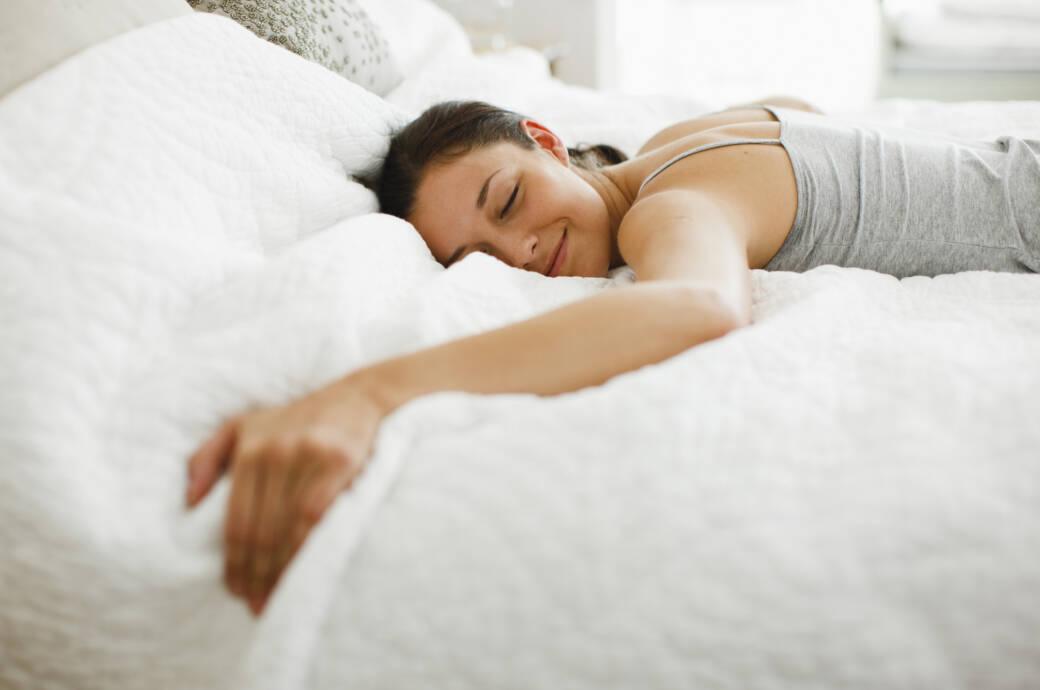 Frau liegt im Nachthemd auf dem Bett und lächelt glücklich