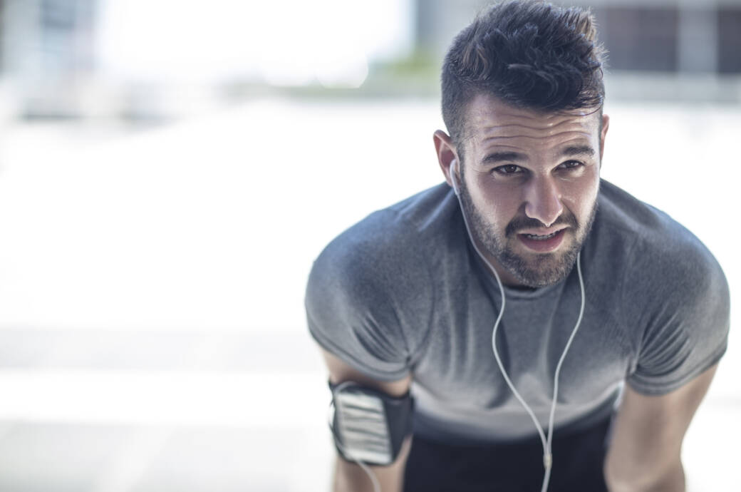 Ausdauertraining soll zu Muskelabbau führen – stimmt das? Junger Mann erschöpft nach dem Joggen
