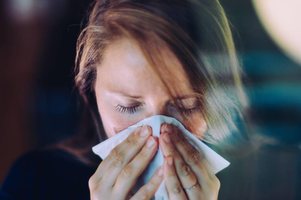 Frau schnäuzt in Taschentuch
