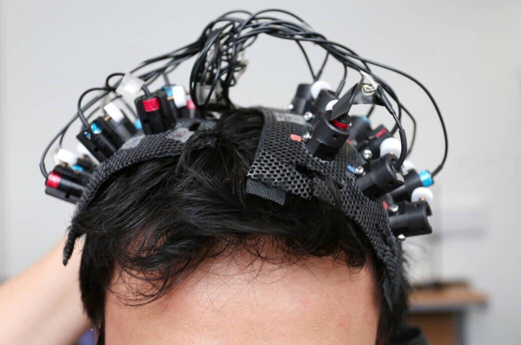 Viele Elektroden, befestigt auf einem Kopf mit schwarzen Haaren