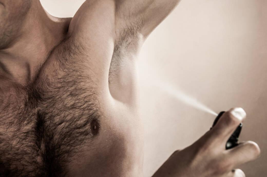 Männliche Achselhöhle wird mit Deo eingesprüht