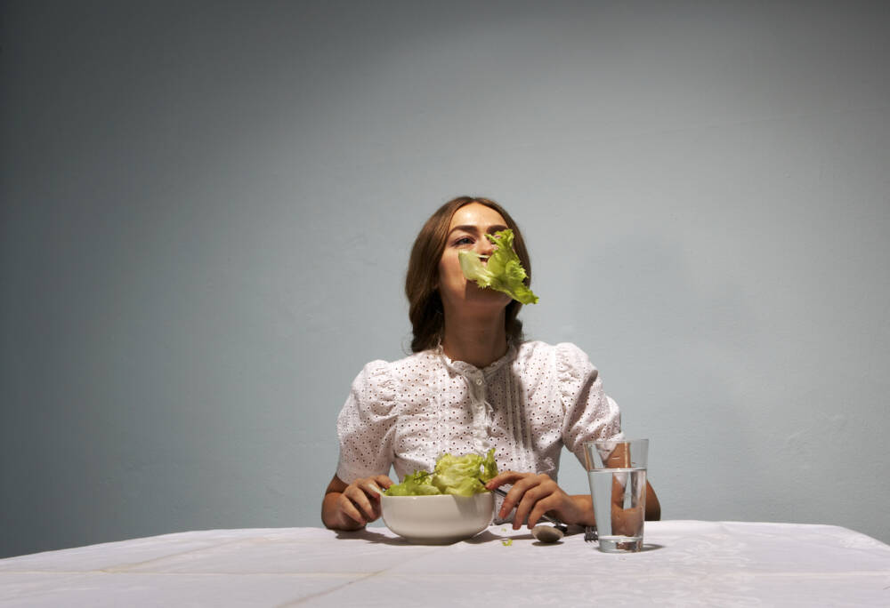 Frau zwingt sich zum Essen von Salat