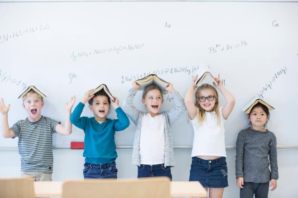 Fröhliche Mädchen und Jungen stehen vor einer Tafel, halten sich jeweils ein aufgeschlagenes Buch über den Kopf