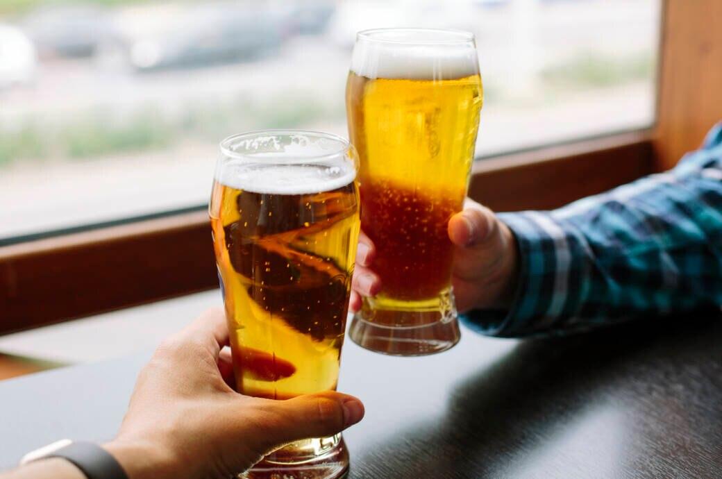 Zwei Männer stoßen mit Bier an