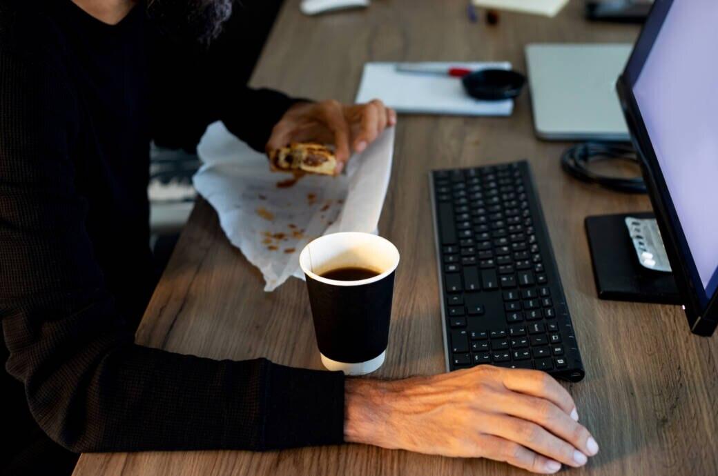 Mann nascht am Schreibtisch ein Croissant