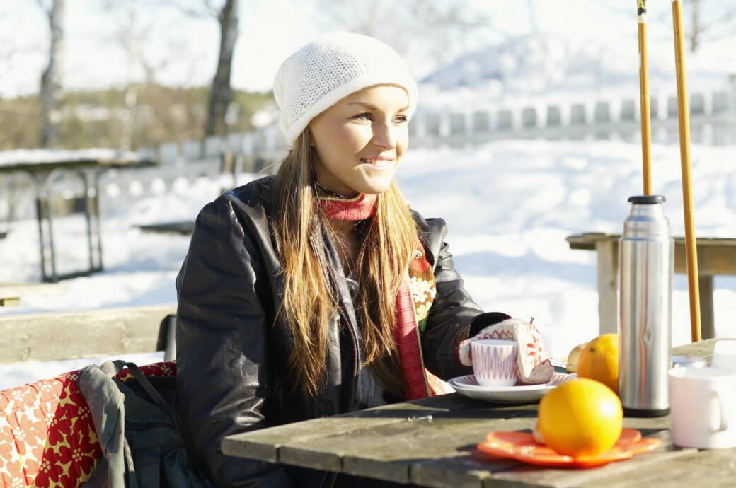 Eine junge Frau macht eine Skipause und trinkt etwas