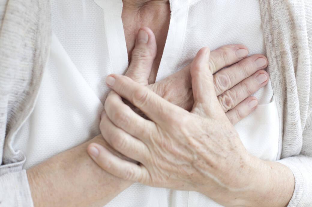 Ältere Frau fasst sich an die Brust