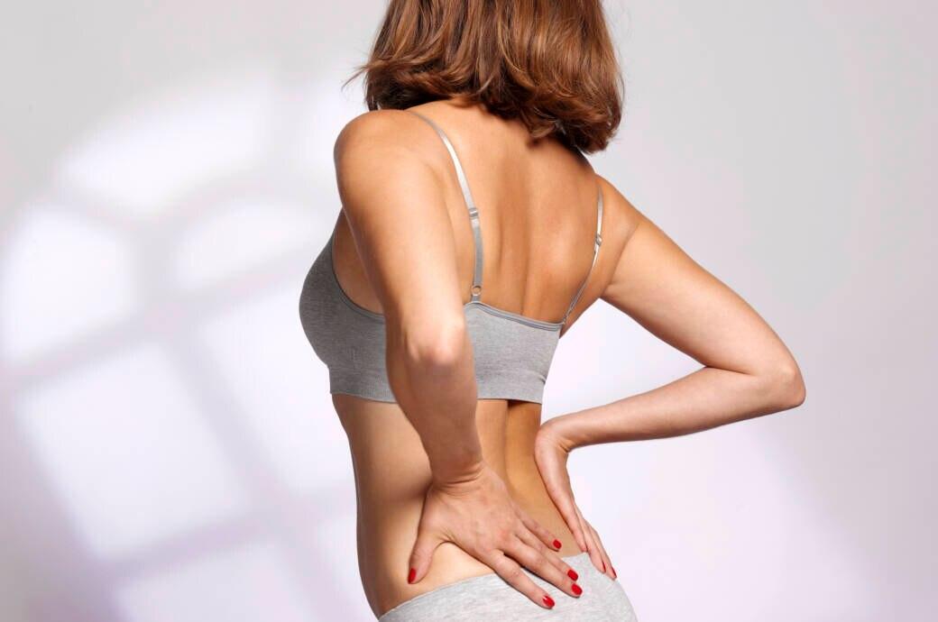 Frau mit Rückenschmerzen massiert sich den Rücken