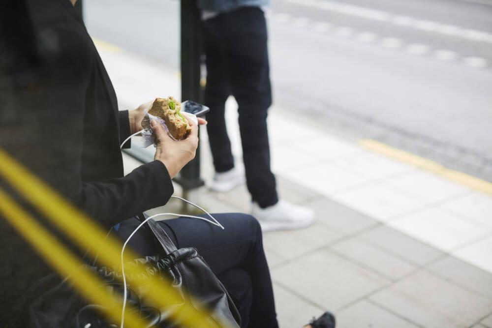 Frau isst an der Bushaltestelle ein Brötchen