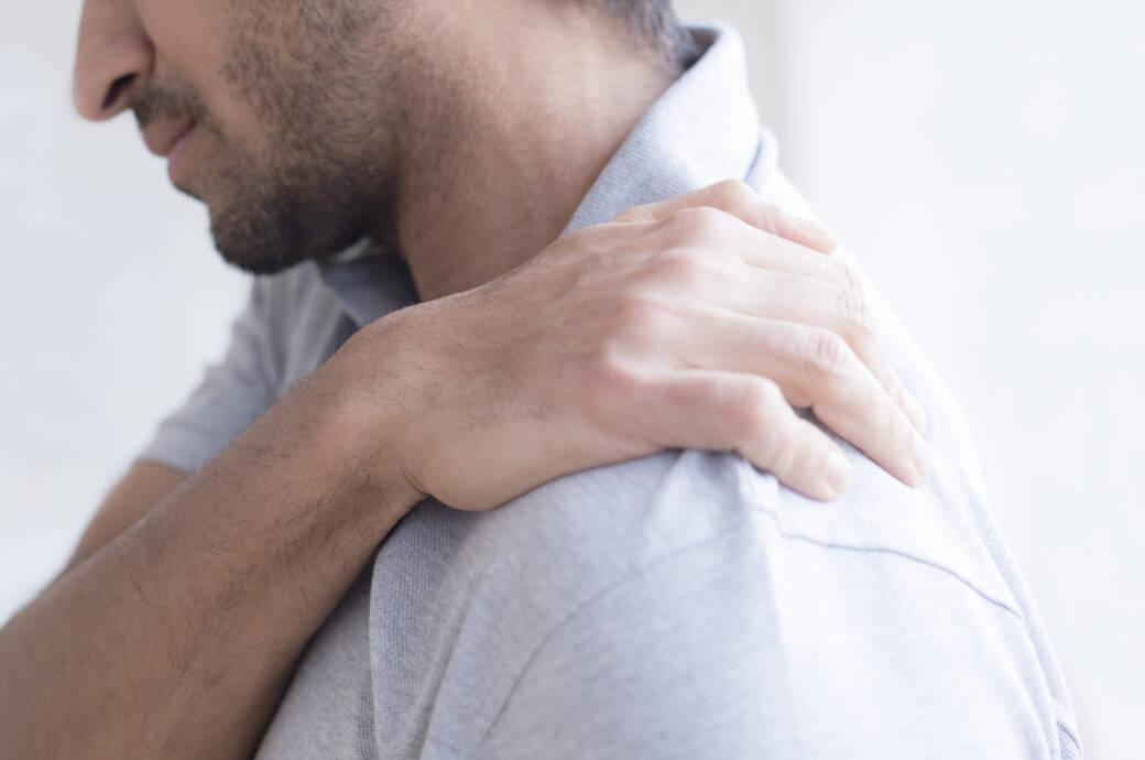 Mann fasst seine schmerzende Schulter an