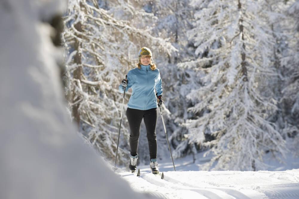 Eine Frau beim Skilanglauf im Wald