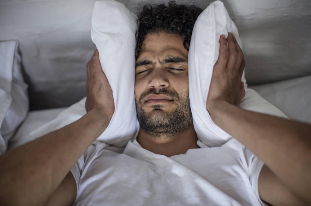 Mann leidet im Bett unter Lärmbelästigung