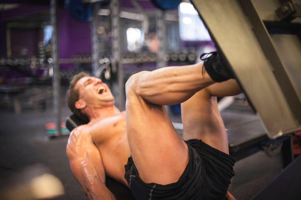 Ein muskulöser Mann trainiert an der Beinpresse