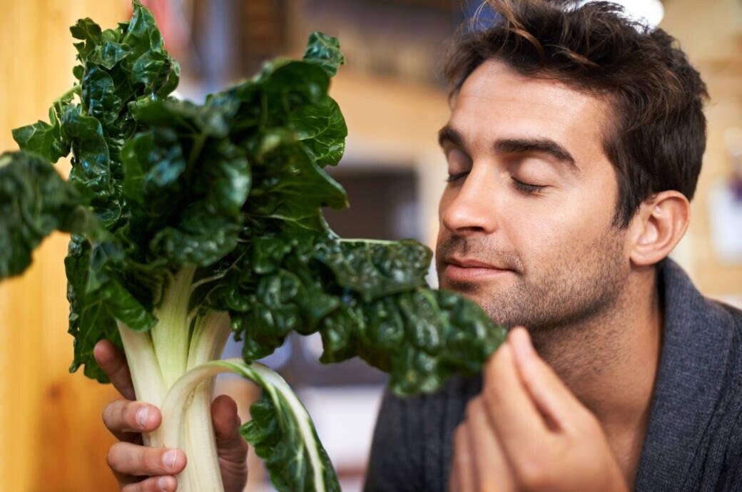 Mann riecht an Spinat