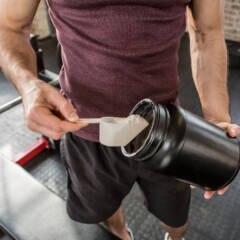 Ein Mann bereitet sich einen Eiweißshake im Gym zu