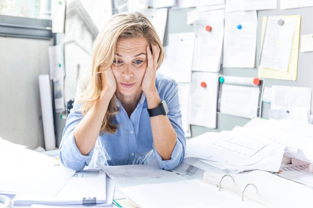 Gestresste, blonde Frau sitzt am Schreibtisch