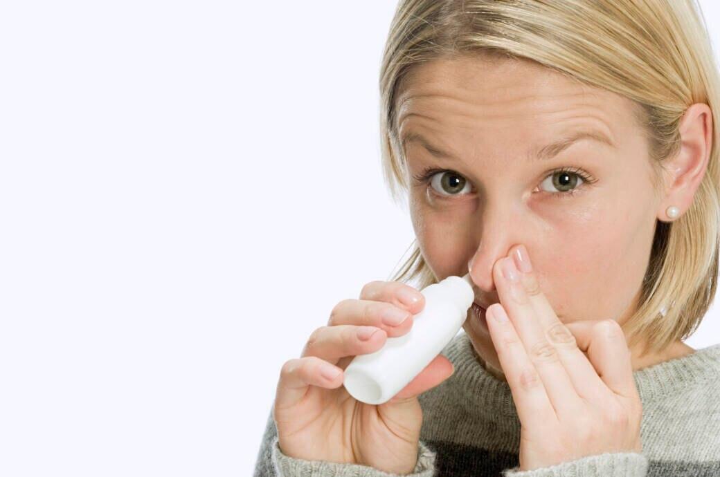Frau nimmt Nasentropfen