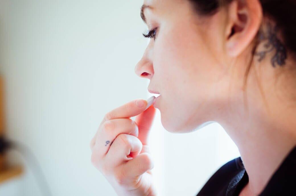 Corona: Frau nimmt eine Ibuprofen