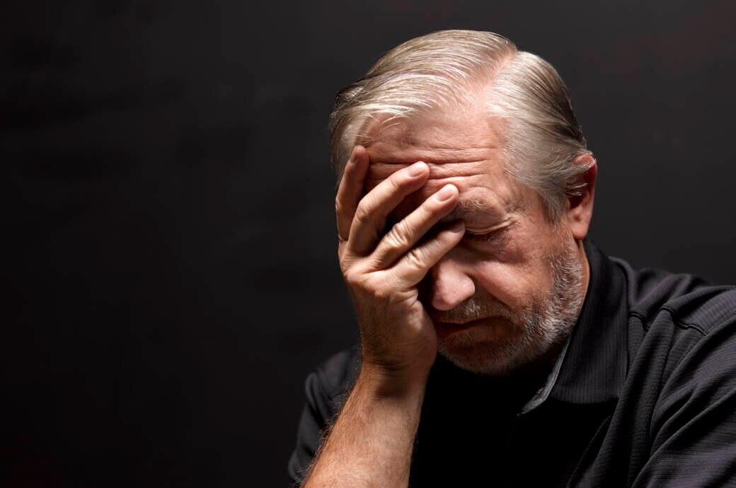 Ein älterer Mann fasst sich an den Kopf