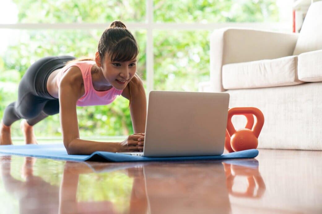 Frau macht Workout vor Laptop