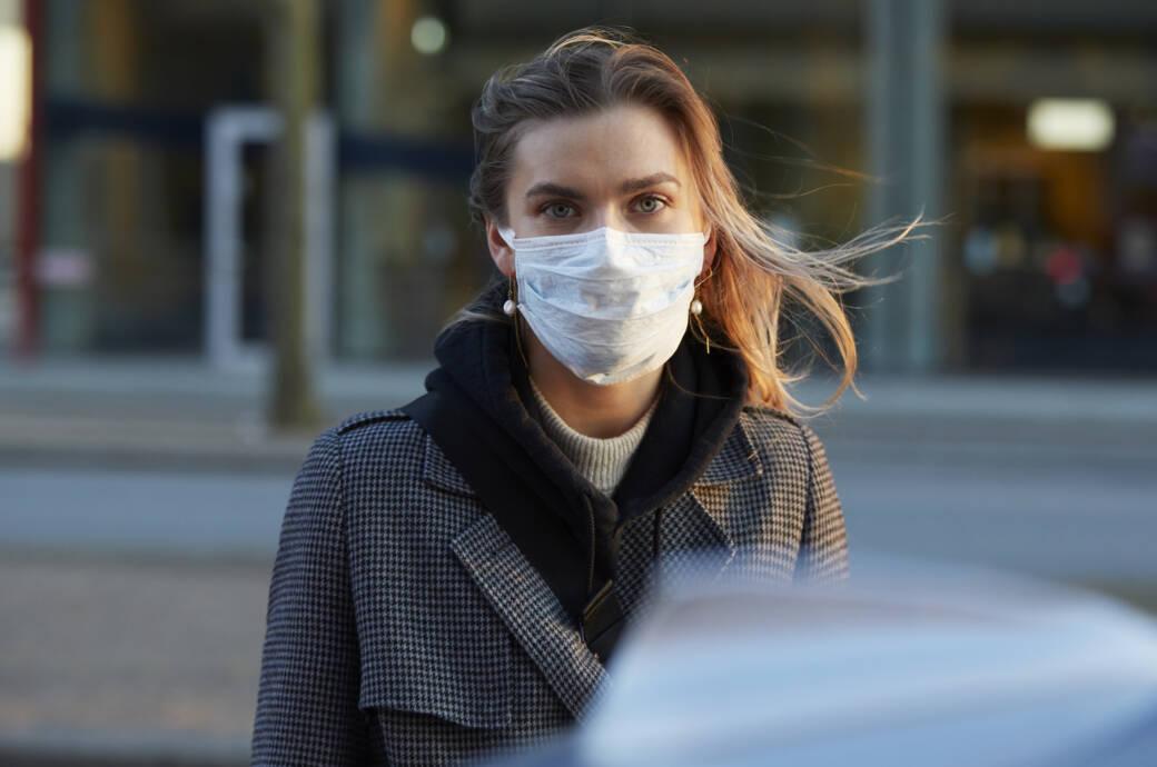 Schutzmaske: Junge Frau mit Mund-Nasen-Schutzmaske