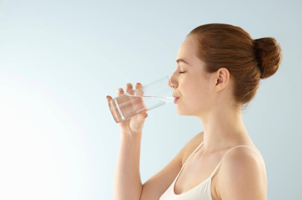 Frau trinkt aus Wasserglas
