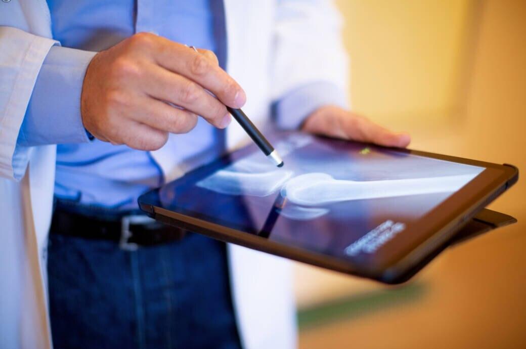 Arzt begutachtet Ergebnis von Stammzellentherapie bei Arthrose