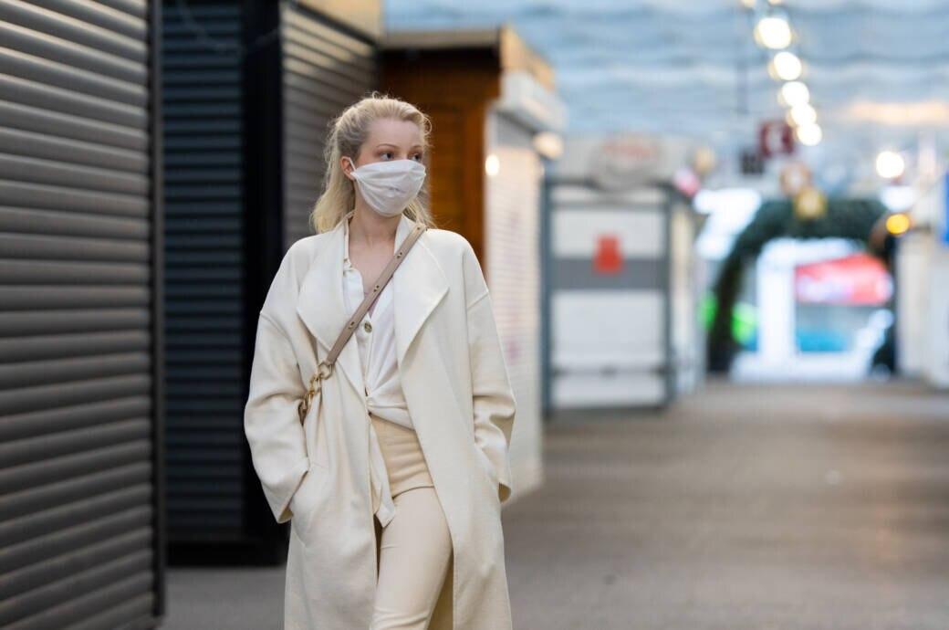 Anti-Corona-Maßnahmen: Eine junge Frau trägt eine Mund-Nasen-Schutzmaske und geht durch eine leere Fußgängerzone