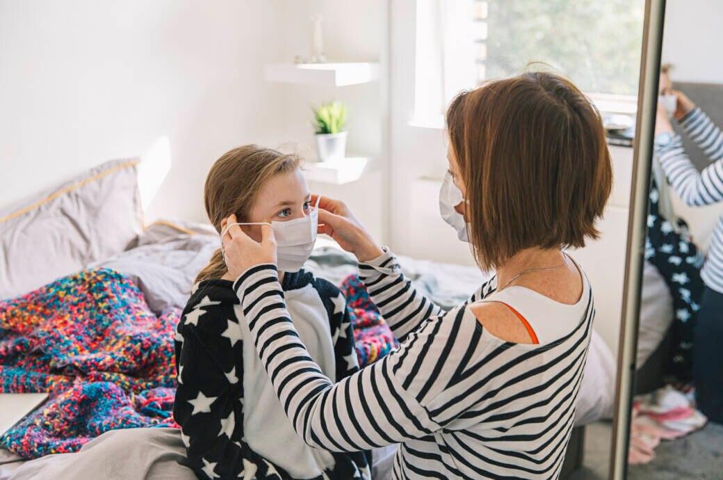 Mutter schützt Tochter mit Maske vor dem Coronavirus
