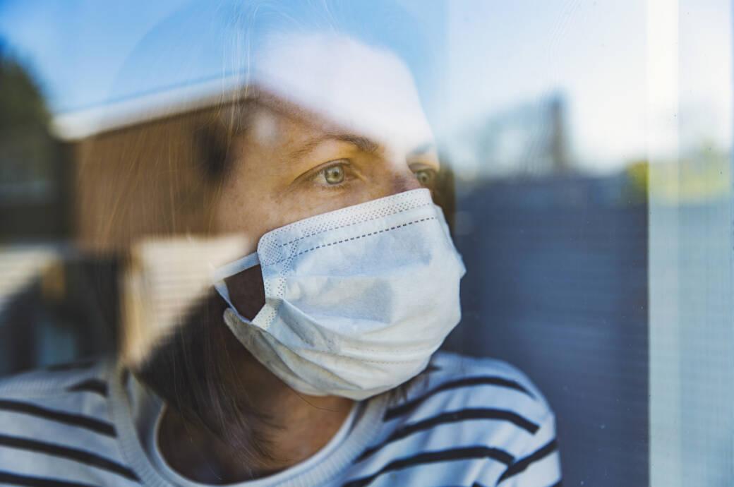 Vitamin D und COVID-19: Frau mit Mundschutz schaut aus dem Fenster