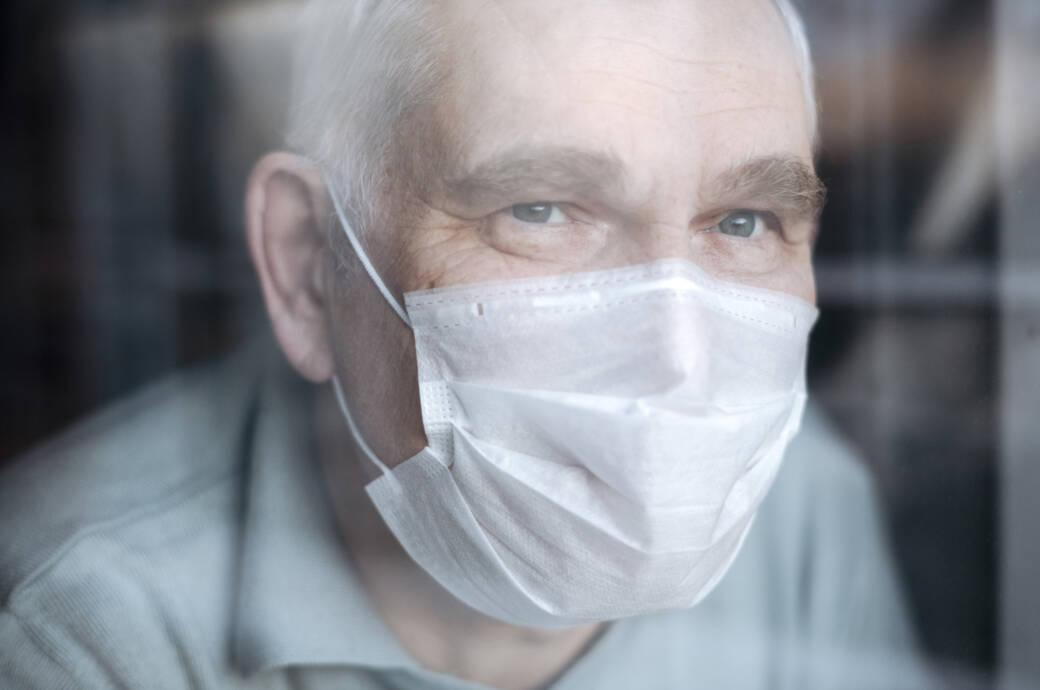 Herzinsuffizienz: Ein Mann mit Mund-Nasen-Schutz hustet in die Armbeuge