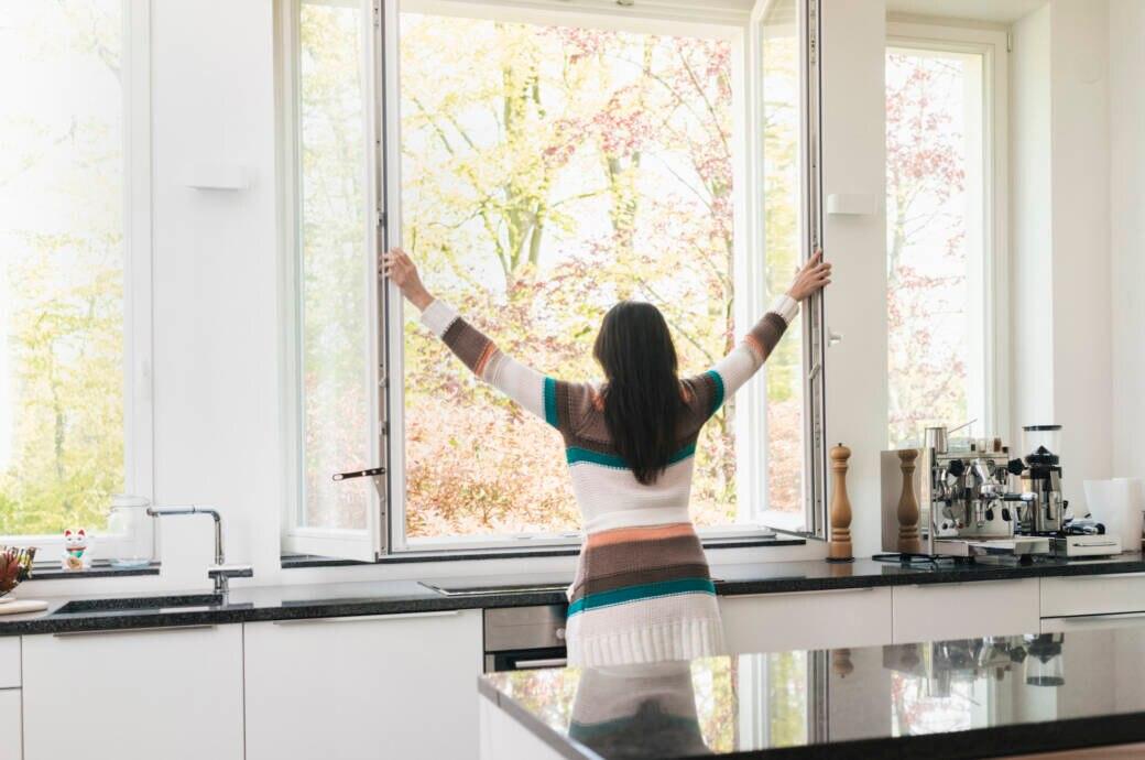 Lüften: Eine Frau öffnet das Küchenfenster