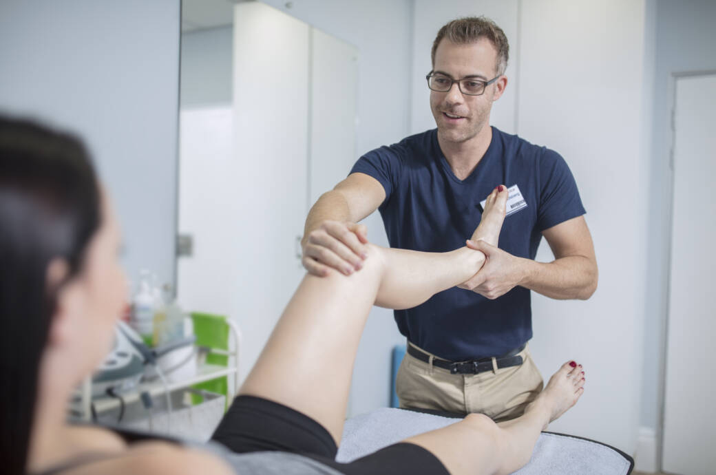 Eine Frau wird von einem Physiotherapeuten behandelt