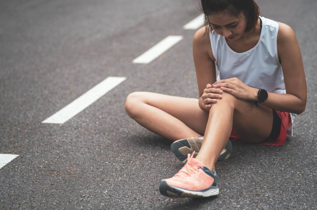 Runners Knee: Eine Läuferin hält sich das Knie vor Schmerzen