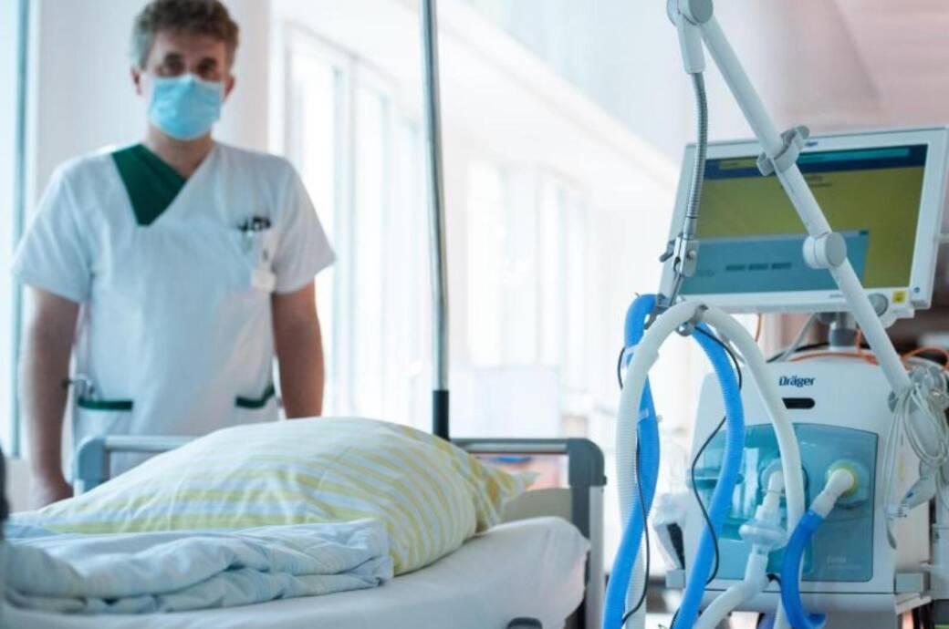 Torsten Blum ist Lungenfacharzt. Er steht neben einem Beatmungsgerät in einem Gang im Helios Emil von Behring Klinikum in Berlin.