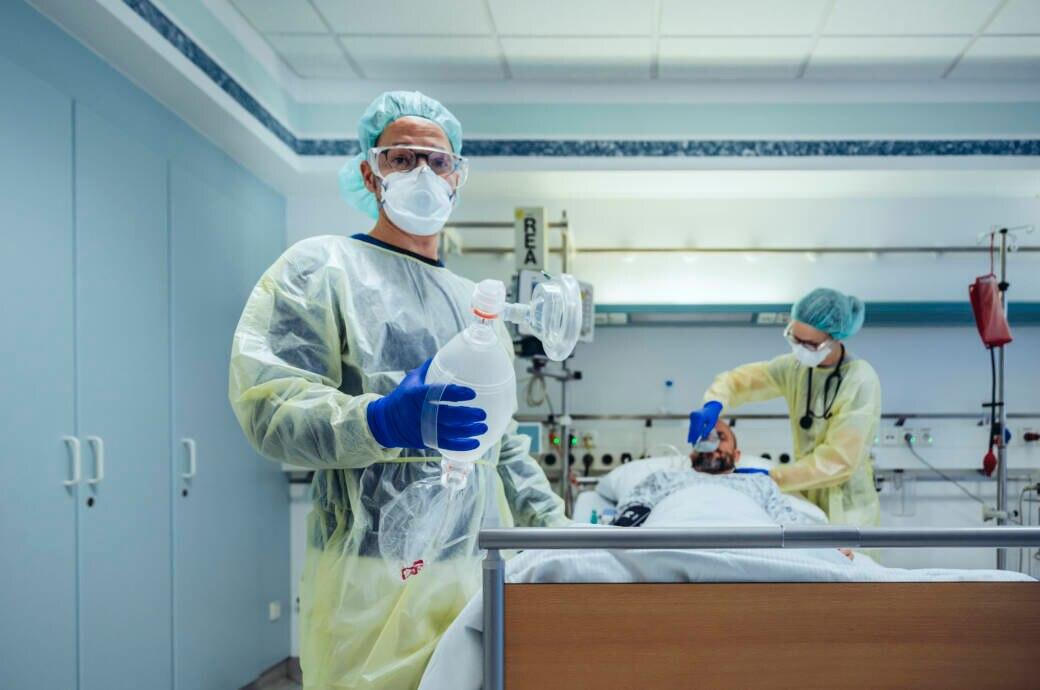 Intensivmediziner wechseln die Beatmung eines Patienten mit Covid-19 von Sauerstoffmaske zu Beatmungsbeitel auf Intensivstation im Krankenhaus, Grevenbroich, NRW, Deutschland (Intensivmediziner wechseln die Beatmung eines Patienten mit Covid-19 von Sa