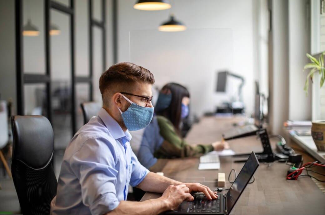 Menschen arbeiten im Büro an ihren Laptops