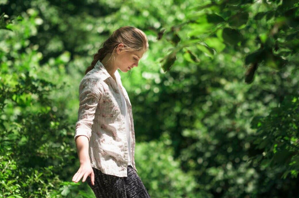 Eine Frau geht konzentriert im Wald
