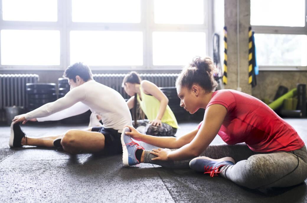 Regeneration nach dem Training: Sportler, die sich dehnen