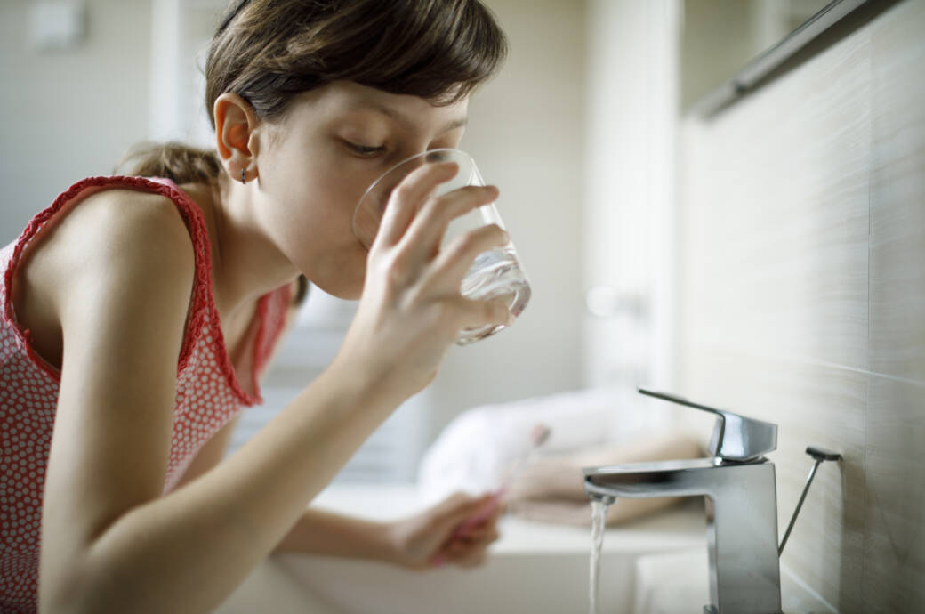 Gurgel-Test Corona: Ein Mädchen nimmt einen Schluck Wasser zum Gurgeln