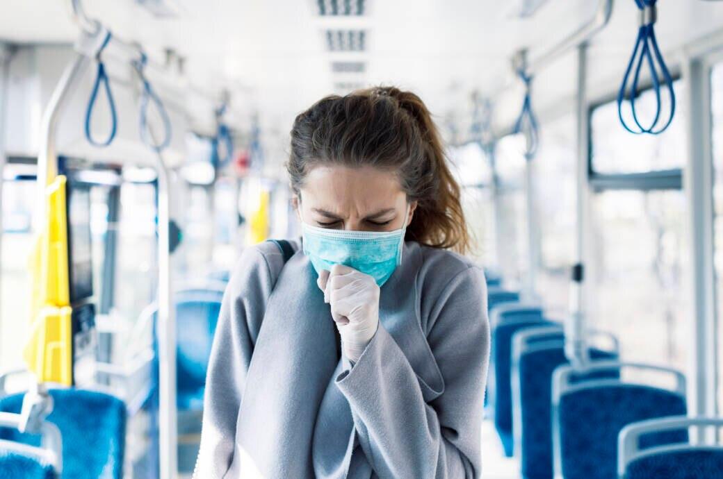 trockene Luft Corona-Infektionen: Eine Frau hustet in ihren Mund-Nasen-Schutz