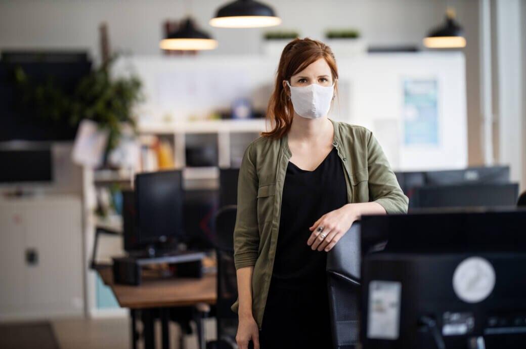 Eine Frau in einem Büro trägt eine Alltagsmaske