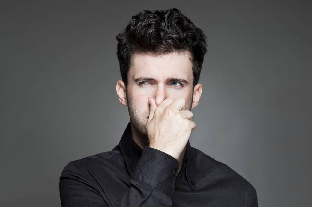 Strenger Körpergeruch: Ein Mann hält sich die Nase zu