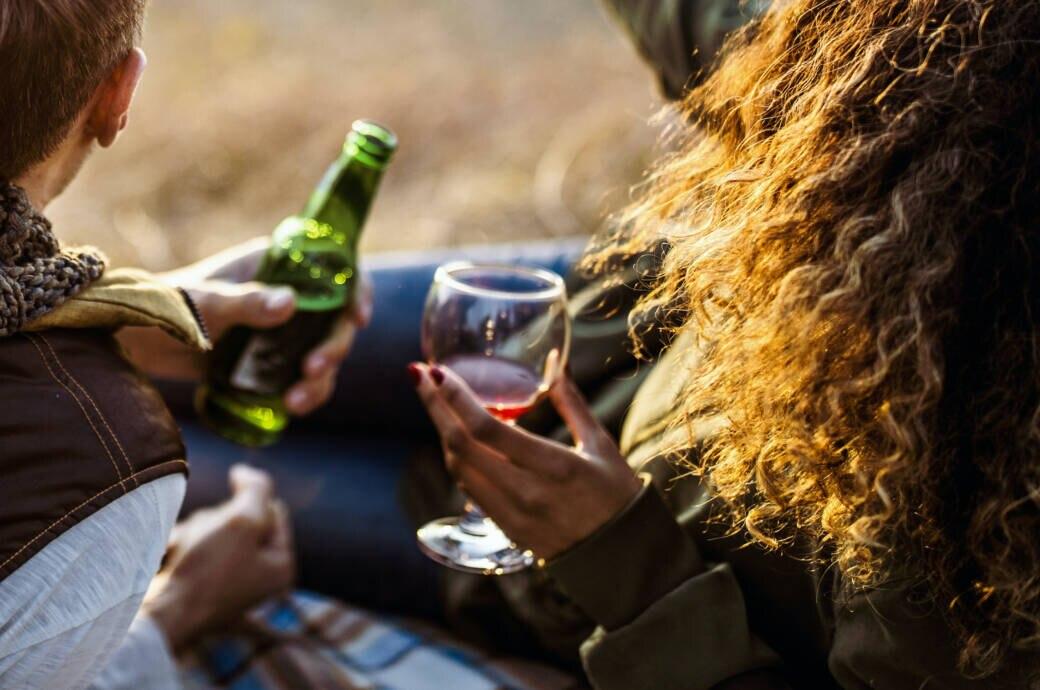 Frau und Mann trinken Rotwein oder Bier – was ist gesünder?
