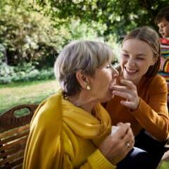 Ein Kind füttert eine ältere Frau