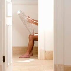 Mann liest Zeitung auf Toilette. Der Verzehr der richtigen Lebensmittel können die Verdauung unterstützen